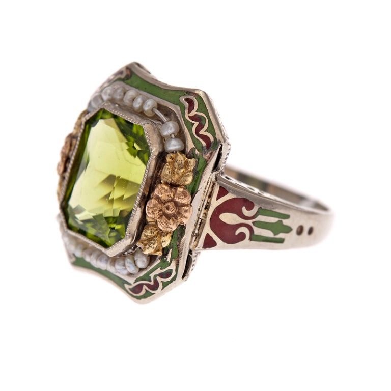 A brilliant display of antique jewelry making: with an intense, dazzling peridot at the center of a crown of rose gold flowers and natural seed pearls and an additional layer of rusty brown and grassy green enamel to complete the package. This