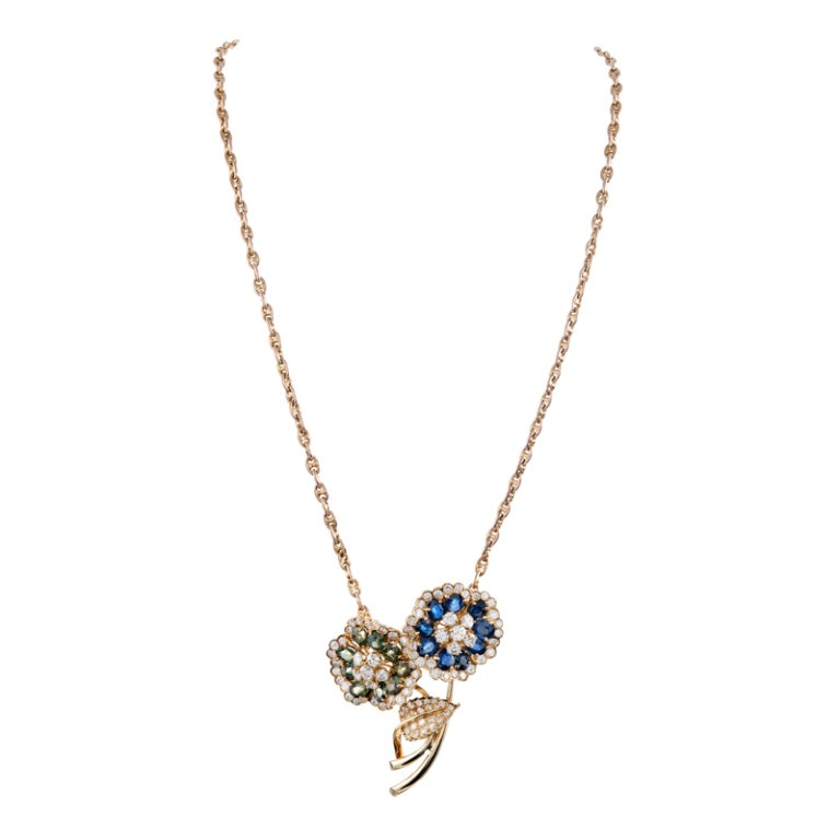 Measuring a substantial 2 inches by 1.75 inches, this lovely enhancer is set with brilliant round diamonds and oval blue- and green sapphires. The back is finished with a space wide enough in which to fit a chain or strand of pearls. This makes a