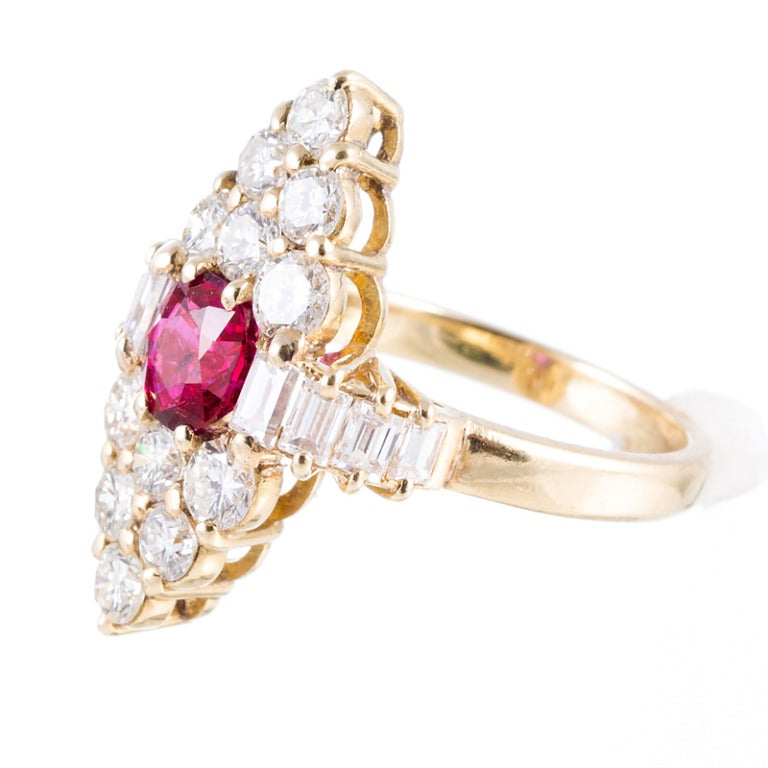 Unusual and architectural elements, featuring a fine 1 carat ruby center and a symbiotic combination of round- and baguette diamonds weighing 2 carats, set in 18k yellow gold.   This ring has a striking look on the finger, yet sits very flat and