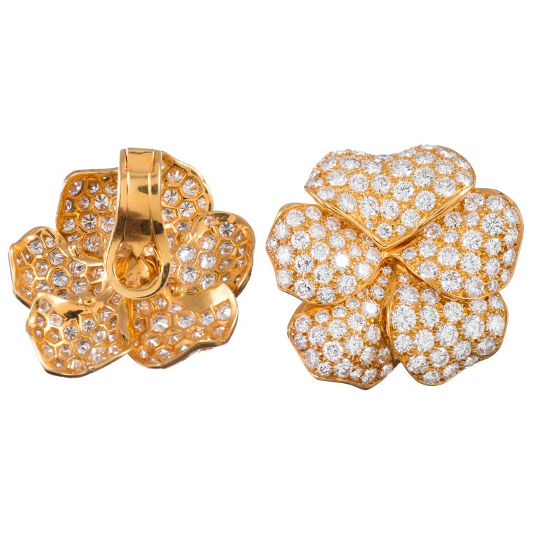 Boasting an impressive 10 carats of brilliant diamonds glimmering on their petals, these flower earrings have sophisticated, organic charm. They are made of 18k yellow gold and are set with 194 round brilliants which grade E-F color and Vvs clarity.