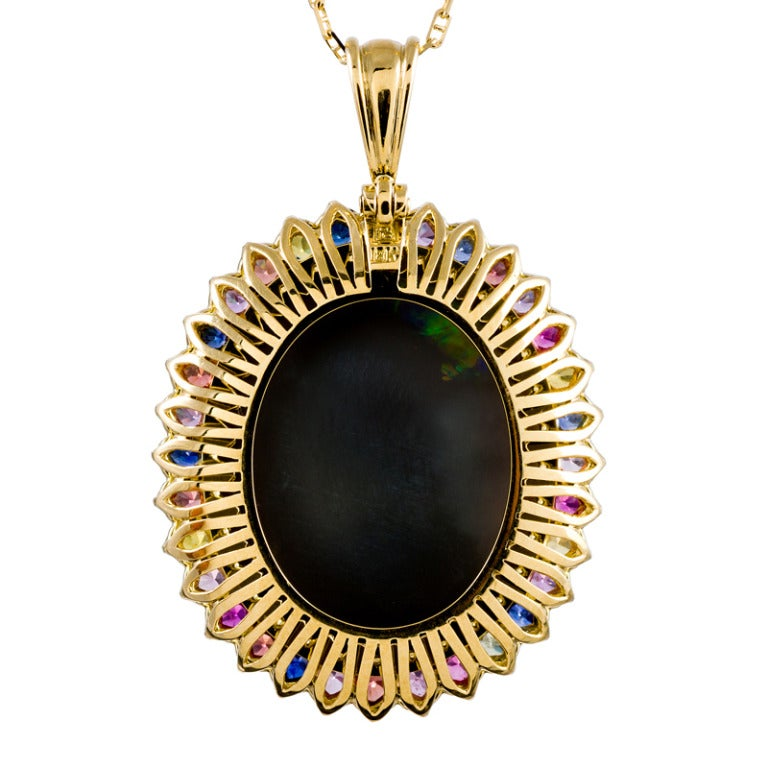Set in 18k yellow gold and surrounded by multi-colored sapphires which lend hints of color and draw out the flashes of luminous pastels exhibited by this magnificent stone. This is a striking piece with a very important opal at its center. Opal