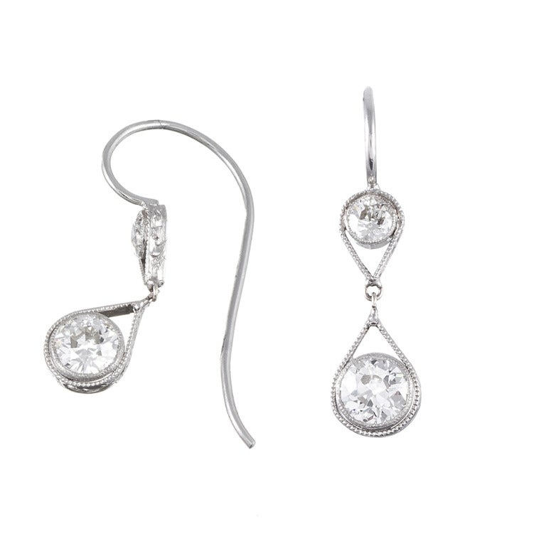 Crafted in platinum with four diamonds weighing approximately 1.50 carats in total. Exquisitely feminine and perfect for every day, these measure 1 inch in overall length.
