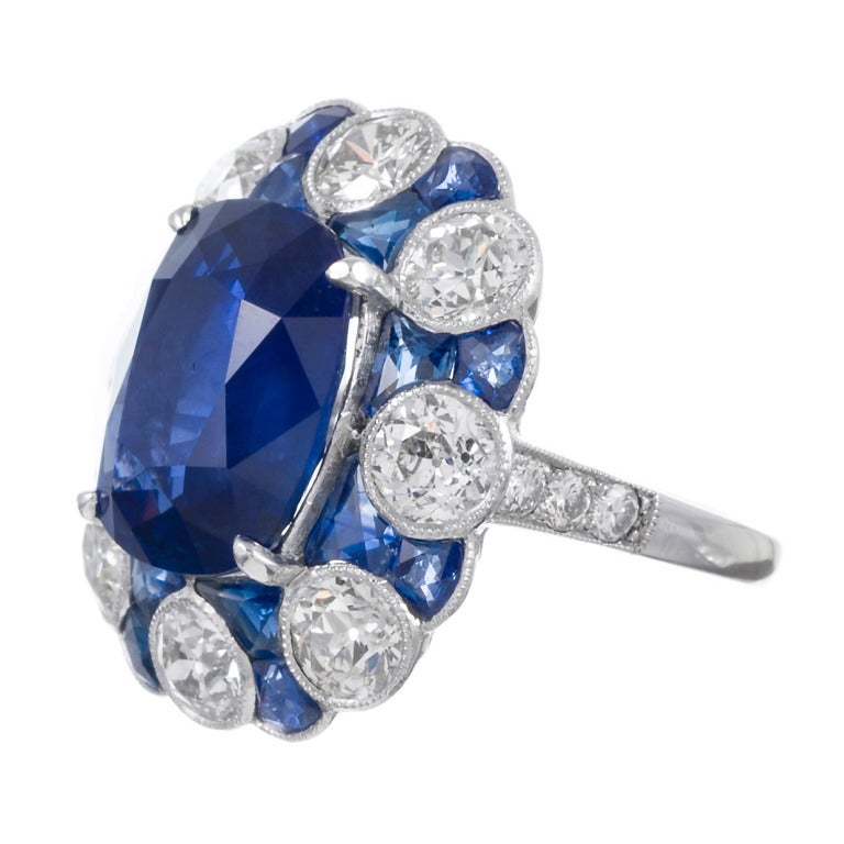 "Platinum ring with a magnificent 10.08 carat sapphire at the center: GIA-certified ""no heat"" and of Ceylon origin. The center stone is set in a cluster style of 3.71 carats of diamonds and 3.02 carats of sapphires, finished with a gorgeous and"