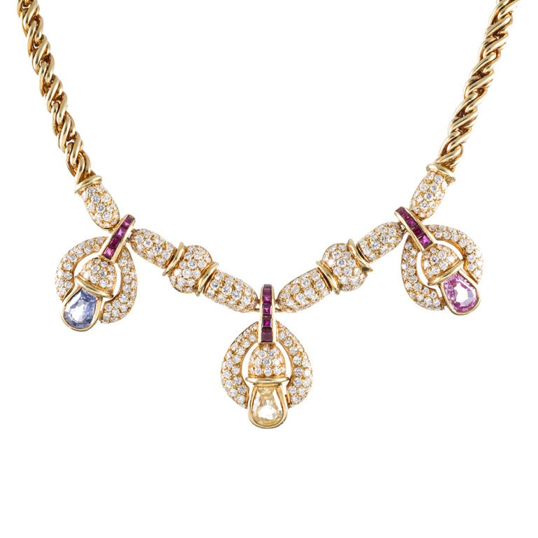 18k yellow gold necklace, resembling Bulgari's iconic designs, set with three bell-shaped drops in a playful display of style and sophistication. The pink-, yellow and blue sapphires weigh 4 carats combined and are topped with .60 carats of ruby and