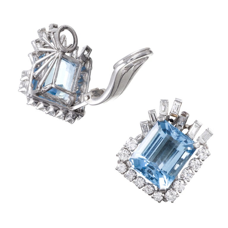 Grand mid-century design, with baguette and round diamonds forming and asymmetrical frame around alluring aquamarine. The aquas weigh 13 carats in total and the diamonds 2.20 carats. Set in platinum, these are currently clips with a large flip-up