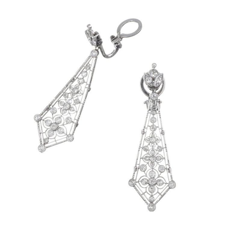 Beautiful and dramatic Edwardian diamond drop earrings featuring a graduated stack of flower-shaped diamond clusters, set inside a swordlike platinum drop. The earrings have fantastic movement and catch the light as they dance about while suspended