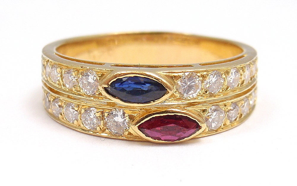 18k Yellow Gold Diamond, Ruby, and Sapphire Ring by Van Cleef & Arpels. With 20 diamonds, VS Clarity, G Color. Total Diamond Weight: .60CT. One Ruby: 5mm in length by 2mm in size. One Sapphire, 5mm x 2mm. 