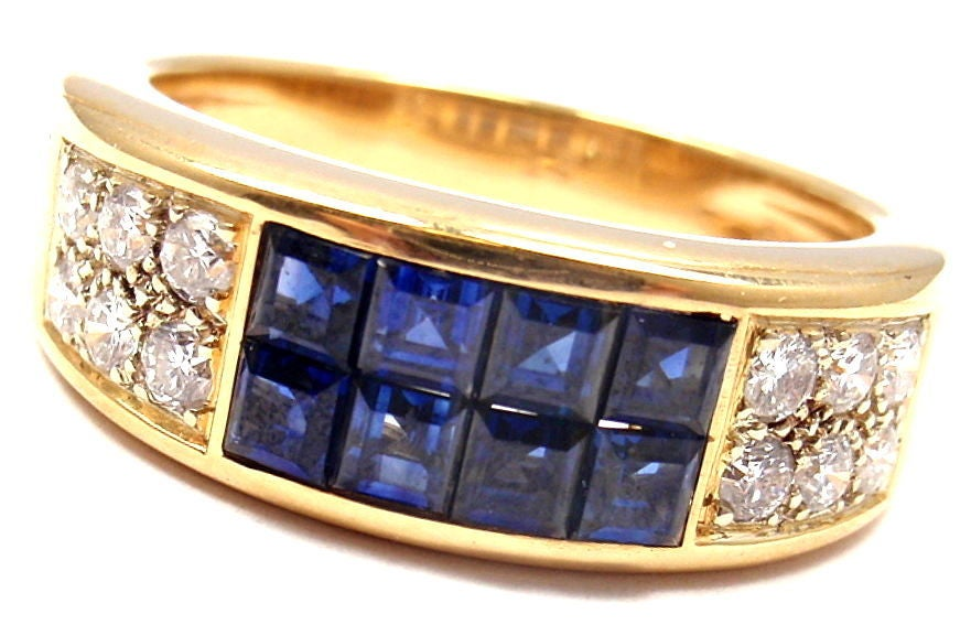 18k Yellow Gold Diamond and Invisible Set Sapphire Ring by Cartier. With 12 round brilliant cut diamonds VS1 clarity and G color approx. .50ct total weight  8 sapphires total weight approx. 1ct  Details: Ring Size:  US 8, europe 57 Width:
