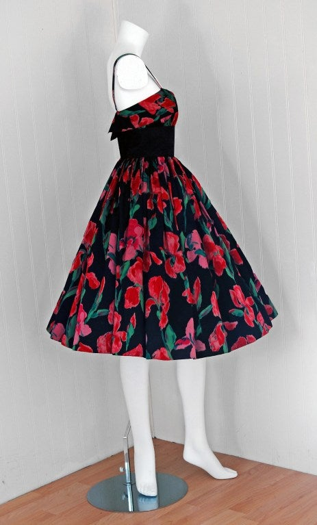 This exquisite mid 1950's Traina-Norell designer dress in watercolor iris-floral print silk satin exemplifies their signature blend of couture-level quality with quintessentially American style— elegant in its simplicity. The bodice has an alluring