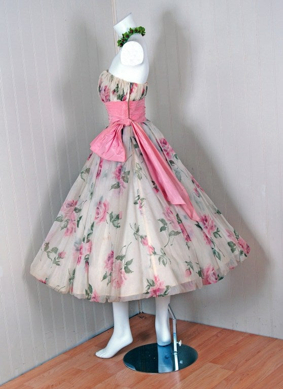 "With its vivid pink-roses watercolor floral print and flawless ""new look"" silhouette, this ballerina cupcake party dress has the casual elegance the 1950's were known for. The artisanship alone is unbelievable. A beautiful scenic-garden print onto"