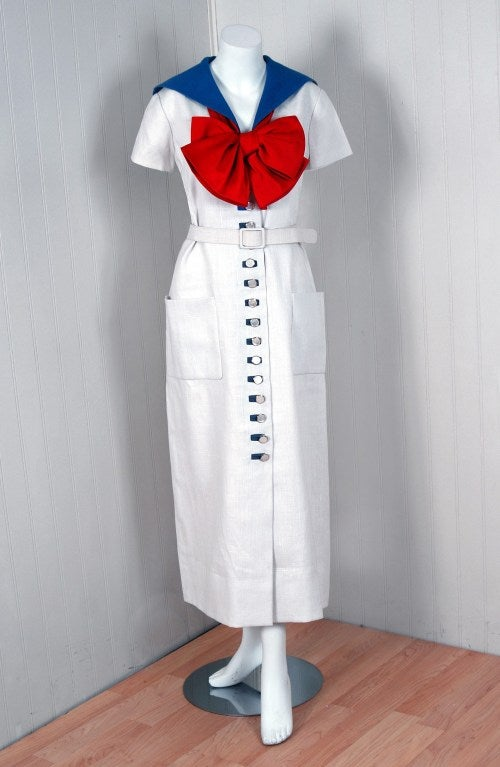 This iconic 1968 Norman Norell nautical sailor dress in mid-weight linen exemplifies his signature blend of couture level quality with quintessentially American style-elegant in its simplicity. The bodice has an adorable detachable red-bow and