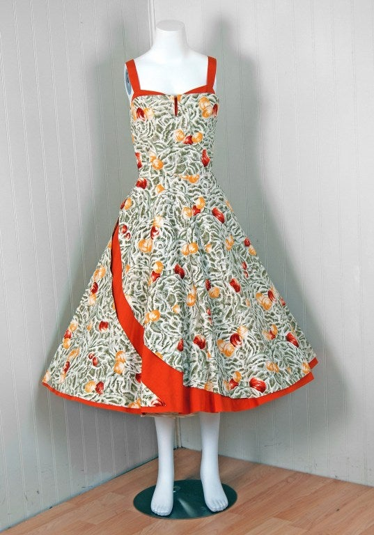 """This beautiful cotton sundress by """"Giara D'Arno"""" is the perfect addition to any summer wardrobe. With its vivid orange seashells novelty-print and flawless styling, this garment has the casual elegance the 1950's were known for. The low-cut plunge,"""