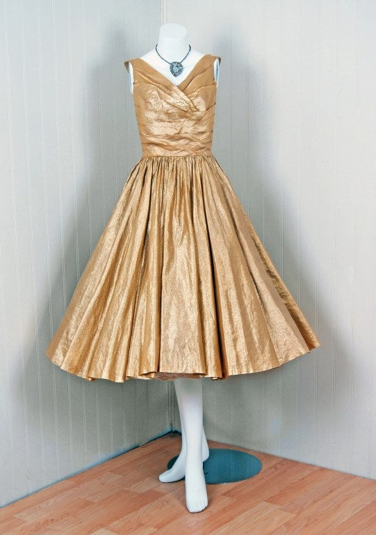 "Glamorous metallic-gold lame party dress by the talented ""Nathan Strong"". It has a Parisian ""New Look"" construction which is still as striking today as it was back in the 1950's. The fitted bodice is meticulously gathered all around. Seductive"