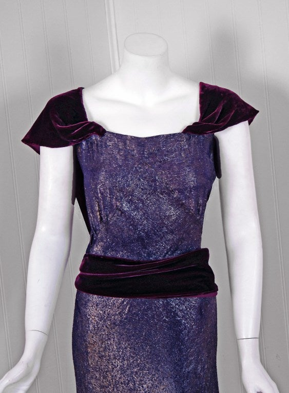 "A luxurious royal-purple shimmer lame gown from the ""Old Hollywood"" era of glamour. The bodice is a low-cut slight cap-sleeve with a plunging backside. The waist is nipped with a stylized silk-velvet sash. The lower skirt is added in pointed inset"