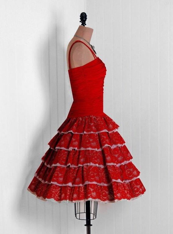 This is perhaps the most darling and flattering 1950's party dress I have ever seen. Fashioned from vibrant ruby-red jersey & organza backed lace, this creation has everything a woman wants. The bodice is a stunning duel-strap ruched design. The