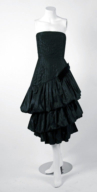 "Stunning 1951 custom-made couture bombshell cocktail dress from the famous ""Old England of Bruxelles"" label. The bodice is an alluring low-cut plunge fully-boned strapless. The graduated gores of silk, double tiered puff skirt give the garment so"