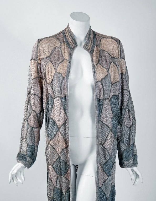 Extremely stylized Art-Deco coat which could easily be a Wiener Werkstatte made for export. Rich polychrome glossy rayon crochet in shades of gray, blue & ivory created to resemble artistic fish scales. The metallic-gold thread accents really