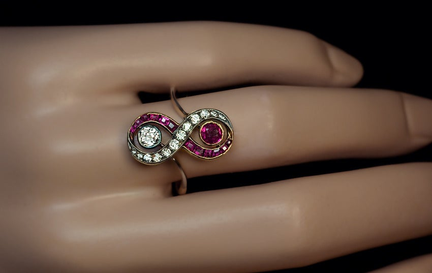 The ring is vertically set with an old cushion cut diamond (approximately 0.31 ct) in a silver-topped gold milgrain setting and an old cut natural ruby (approximately 0.25 ct) in a milgrain gold setting,  flanked by two interlaced scrolling rows of