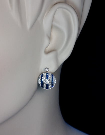 Portuguese, circa 1920s.  A pair of finely crafted disc-shaped platinum-topped 19K gold earrings. Each earring is centered with a sparkling old European cut diamond in a milgrain setting.  The background is designed with three vertical rows of