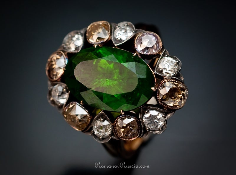 The ring is set with a very rare Ural demantoid garnet weighing 5.1 ct, encircled by a single row of six white and six fancy colored old cut diamonds with an approximate total weight of 1.80 carats.  The ring comes with GIA and AGL reports for the