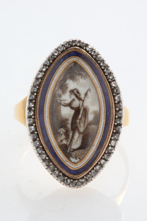 The Georgian jewel is a navette shaped lover's ring with sparkling rose diamonds on the outer perimeter. Gold frames both blue and white inner borders. Under pure rock crystal, a youthful, smiling, shepherdess is intent upon carving the initials of
