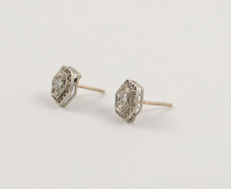 A Lace like platinum and a white gold double frame securely holds a  .15ct european cut diamond. The diamond is sparkly and bright in a design that enlarges their appearance.  These are wear with everything  earrings that have the advantage of being