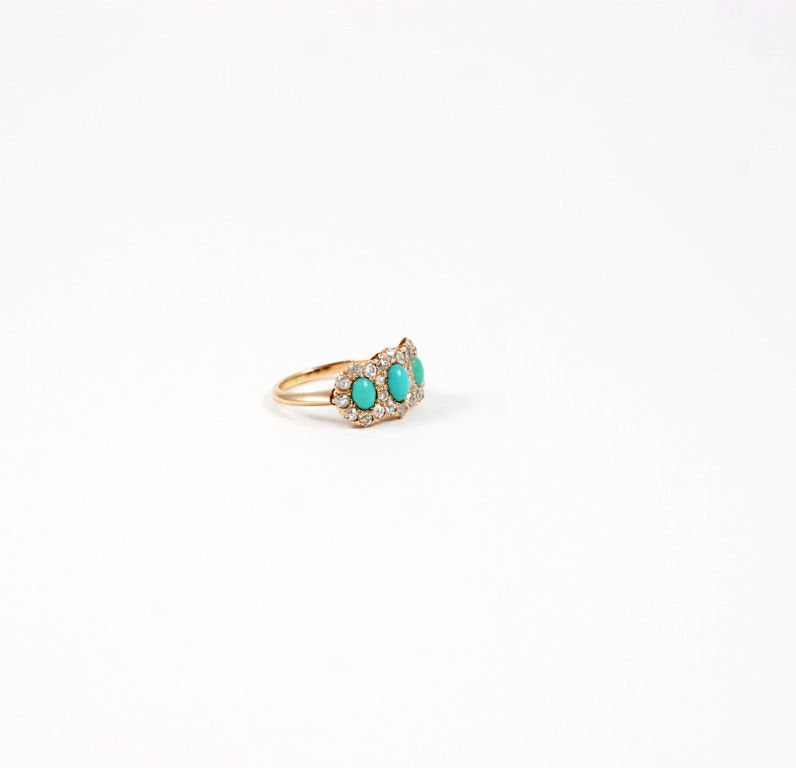 Natural oval turquoise stones are warmly nestled amongst the brilliant white shine of small diamonds in this ring that resembles a crown. The diamonds are rose cuts that emit so much light, they look to be brilliant cut stones. The backs of all
