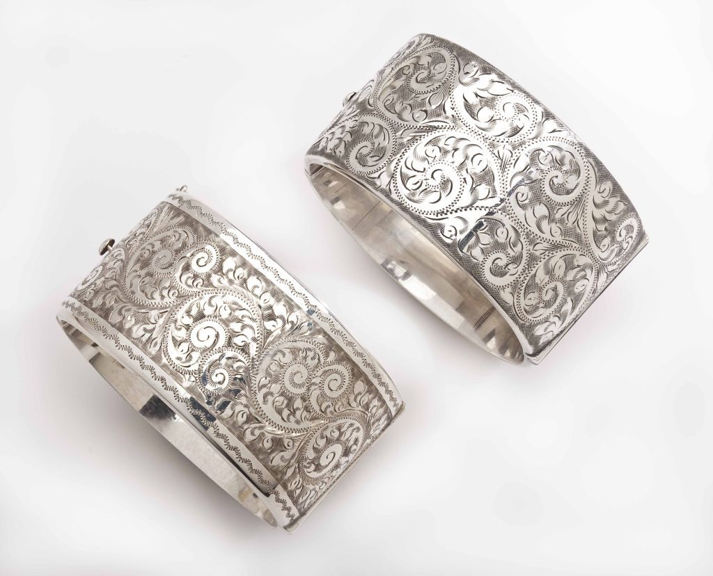 Sterling silver cuffs,1 1/2 inches wide, are florid enough to make a strong show of themselves separately. When purchased as a pair, the drama of wearing one on each wrist is exciting.   Paisley forms made of fronds, and abstract flowers cover the