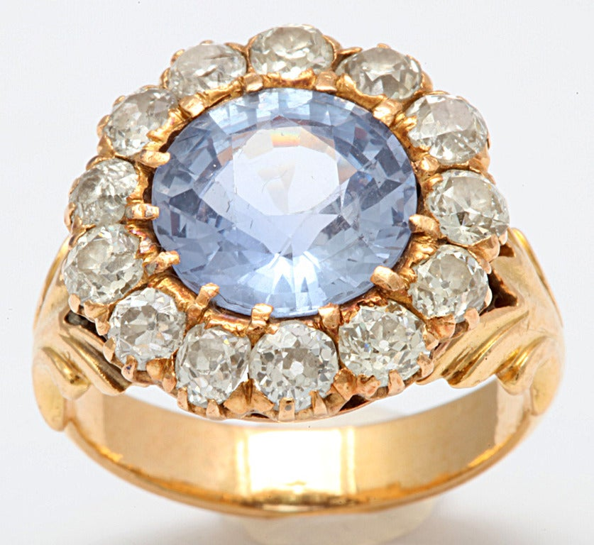 A ring that stuns, A heavenly blue gem framed with stars of flickering diamond . The blue gem, 4.35 cts, is a natural cornflower blue sapphire, a rich, medium blue color with a touch of lavender in the mix. It is rare to find a sapphire that is not
