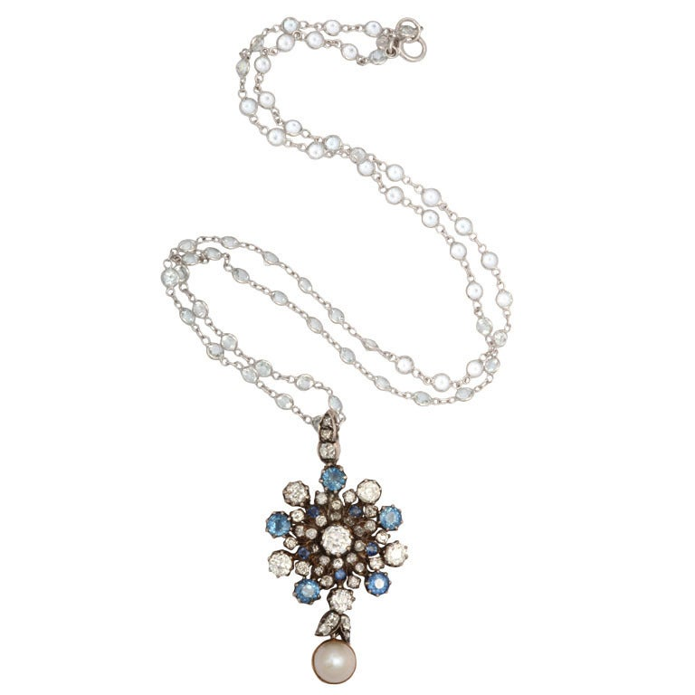Natural cornflower blue sapphires, and bright european cut diamonds send flashes of light from this small jewel that bursts with color. The stones are set in open, beautifully jeweled gold settings allowing them to gather and return all available