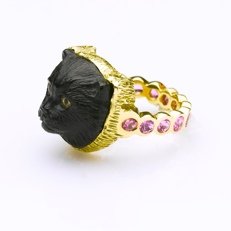 Hand carved jet cat's head with painted crystal eyes set in 18karat gold frame with 14 pink sapphires set in the band. 1.40cts total weight, sapphires.17 x 17 x 10 mm stone size.