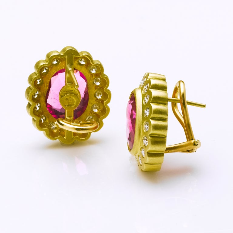 Dazzling cushion cut pink tourmaline earrings with 18karat yellow diamond surround. Omega clip back for pierced ears.  4 cts pink tourmaline each Total weight diamonds 1.92cts