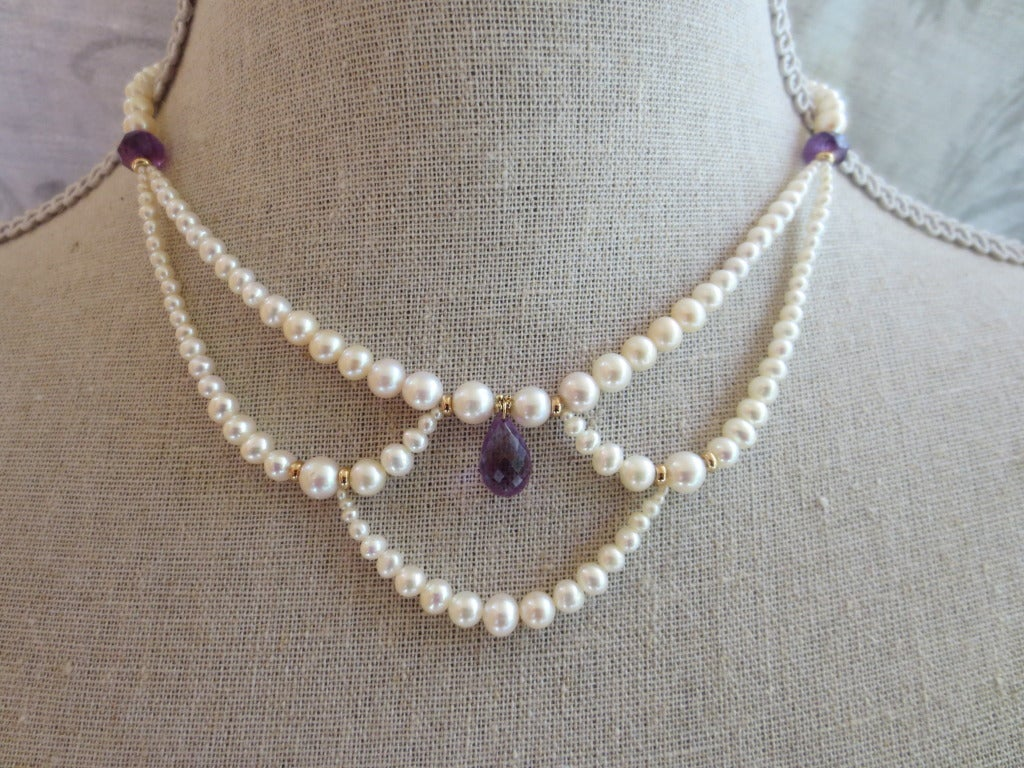 This romantic, graduated pearl necklace has a delicate amethyst teardrop brilolette and 14k yellow gold beads and clasp The graduated white pearl drapes of the 16 in. necklace create highlights the grace and elegance of the neckline. Each pearl was