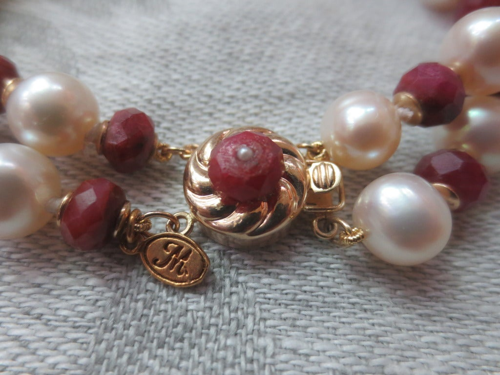 This white pearl and faceted ruby beaded bracelet with 14k yellow claps is an elegant piece that can dress up or down and outfit. The bracelet is made of two strands of 6.5 - 7mm white round pearls, rough faceted ruby beads, and 14k gold findings.