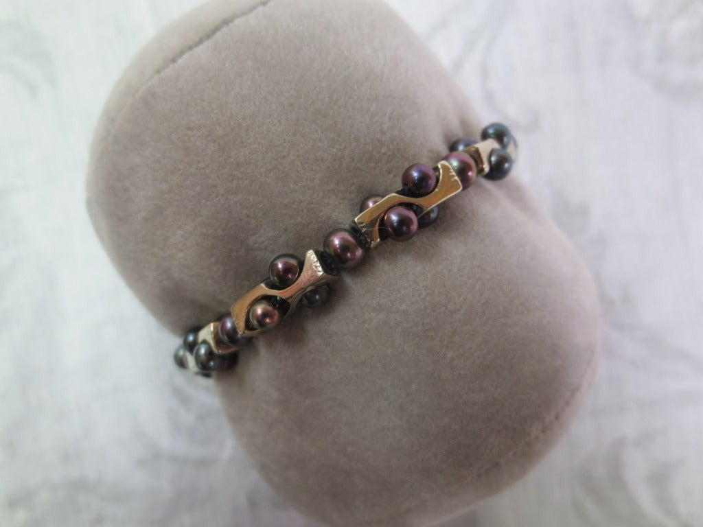 This geometric infinity unisex bracelet is styled with rectangular 14k white gold structural beads and black pearls. Small black pearl beads are
