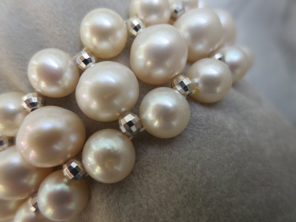 The intricately hand woven white pearl bracelet is accented with 3mm sterling silver faceted beads. Each white pearls was hand chosen by Marina J., running from 5mm and 7mm in diameter, creating a bracelet 3/4