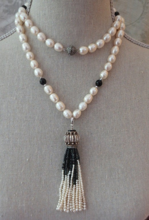 This tassel necklace is reminiscent of the deco style of the 1920's. Made of pearls and onyx, the piece has an elegant and stunning black & white combination. The necklace is made of baroque style cultured pearls, faceted silver beads, and black