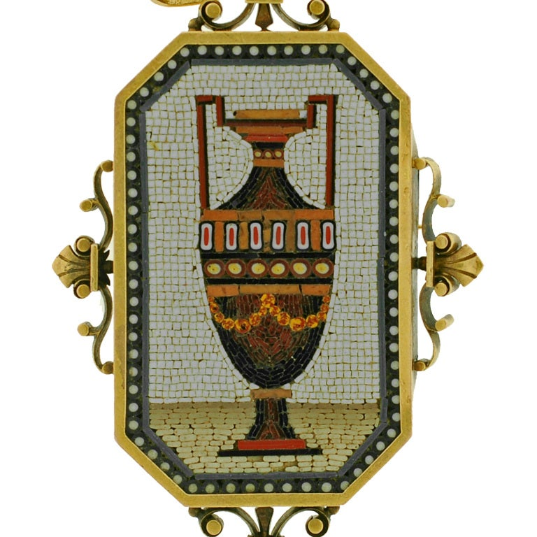An absolutely fabulous micro mosaic pendant from the Victorian era! Tiny tiles with vivid colors of glass have been hand set into the image of an ornate urn which sits at the center of this piece. The urn is wonderfully detailed and rests on a beige