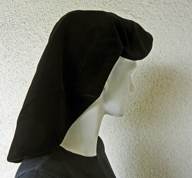 An Adrian Original black soft velvet snood, simulating a nun's hood.  Supported by an exterior circle.  Both snood and circle are lined with net.  A very simple but brilliant design with strong silhouette.  Possibly inspired by a nun's habit.  Size: