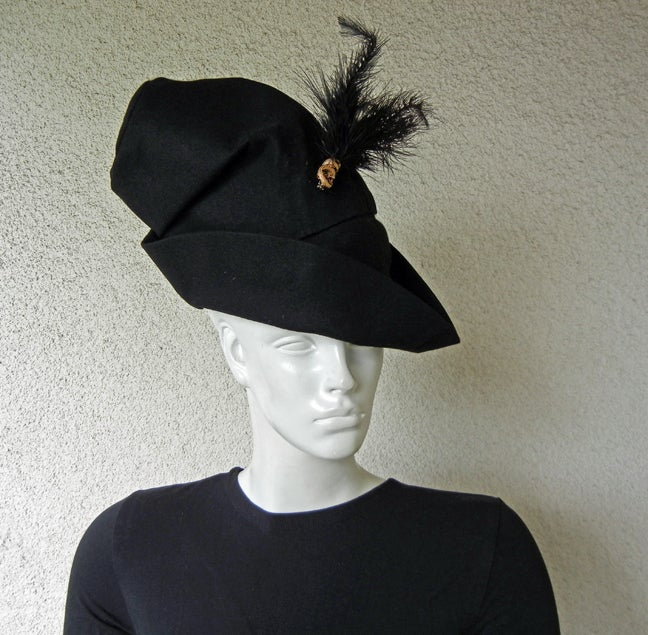 Adrian Custom/Julius Garfinkle dramatic black wool felt hat evoking image of Robin Hood and Sherwood Forest. Anchored on side with gold trim and feather.    Size: 22-23