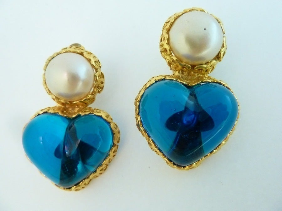 "These vintage signed Chanel earrings feature striking blue Gripoix glass shaped in a floating heart, with cabochon cut faux pearl accents in a gold-tone setting. In excellent condition. these clip earrings measure 1 ¾"" x 1 1/8"" and are signed Chanel"
