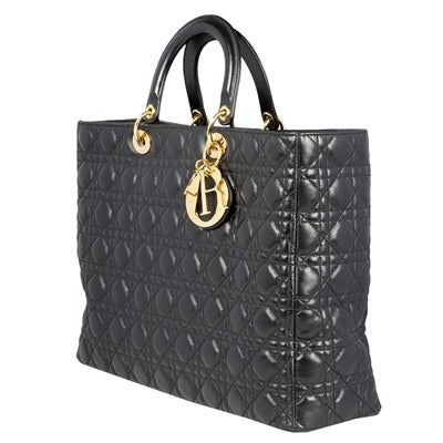 Lady Dior handbag in black leather from Christian Dior with the traditional letter charms, gold-plated hardware and zip closure. Lined in red logo-jacquard fabric, the bag's interior has one zip pocket. This piece also comes with a detachable long