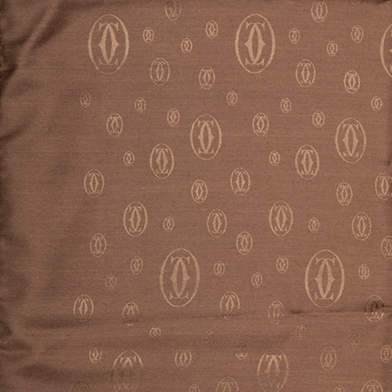 Brand new silk and wool blend scarf from Cartier featuring the Cartier logo in tan over a dark brown background. These colours are inverted on the other side of the scarf.