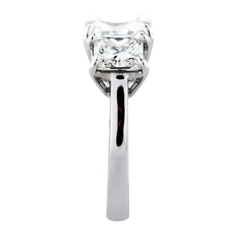3 Stone Engagement Ring with Square Modified Brilliant Princess Cut Diamonds. Stones are set in a Handmade Platinum Setting. The center stone is a 1.51ct Princess Cut Diamond, H in Color and VS1 in Clarity. It measurements are 6.39 x 6.28 x 4.52 mm.