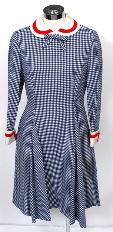 Not so sweet and innocent? Ramp up this demure navy blue/white checked long sleeved, knee length sailor dress from Mollie Parnis with linen peter-pan collar and french cuffs trimmed in red braid, fitted bodice through waist with two full length