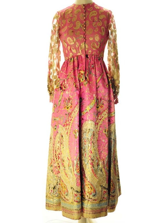 Beautiful vintage Oscar de La Renta pink evening gown with metallic gold embroidery bodice and brocade skirt. This dress features empire waist and gathered skirt, sheer long sleeves with gathered cuffs and covered button and loop front closure.