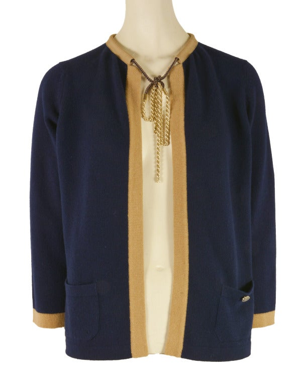 This Chanel cardigan is 100% soft cashmere and is presented in Navy Blue with Tan trim.  It features two front pockets, the left pocket has a CC emblazoned button.  It also has a rope chain.  This beauty originally retailed for $2825!!!