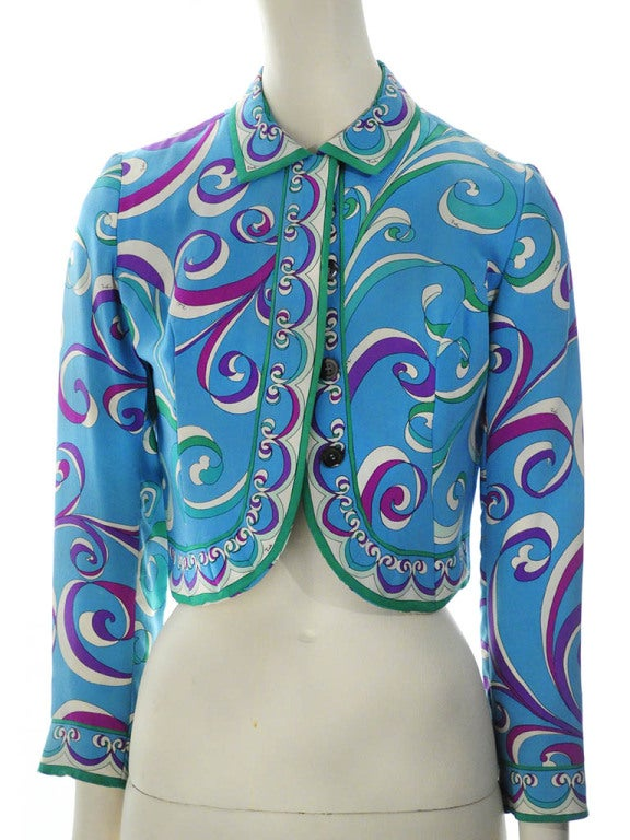 "Vintage Emilio Pucci bolero jacket in teal silk with purple, fucsia, green and mint iconic Pucci print ""Made in Italy for Lord & Taylor."" Jacket features border trim on collar, sleeve and tulip hem, center back inverted pleat/vent and four hidden"