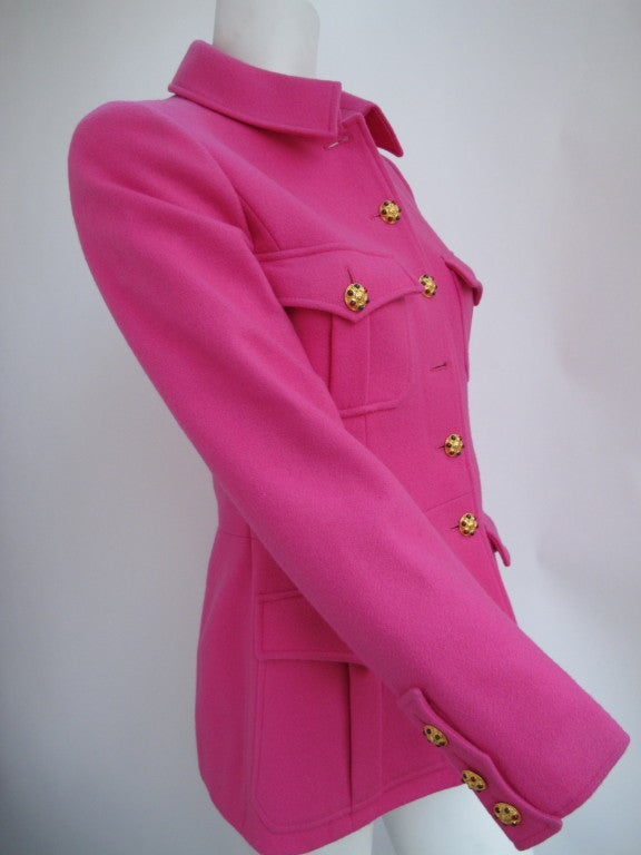 This is a Chanel Boutique fuchsia-colored military style jacket made from 100% wool melton - collection Au '96. The jacket is beautifully constructed and features details such as sixteen gold Gripoix buttons, 100% silk pink Chanel logo fabric lining