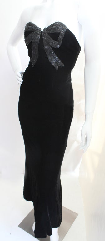 80s Oscar de la Renta strapless velvet column dress that flairs at the bottom. The gown's main attraction is a bugle-beaded bow embroidered onto the chest. Fully lined including a built-in bra top. The sizing tag is a 6 but it fits more like a